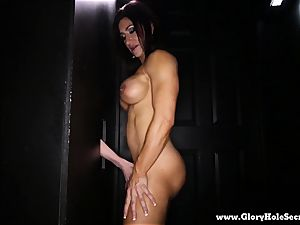 Muscle babe guzzles weenie in gloryhole