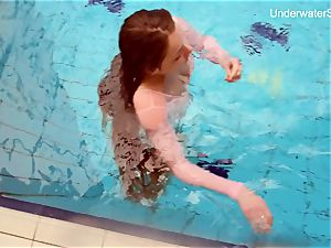red-haired Simonna displaying her assets underwater